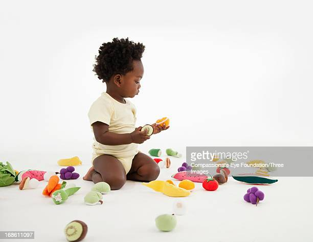 Baby playing with toy fruit