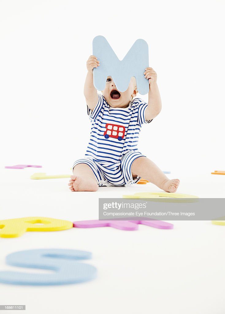 Baby playing with toy letters : Stock Photo