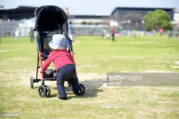 A baby pushes her baby carriage in a park