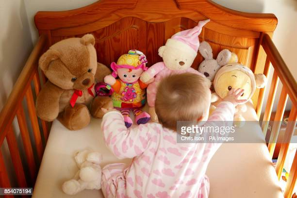 A baby reaches out to a teddy bear in her cot