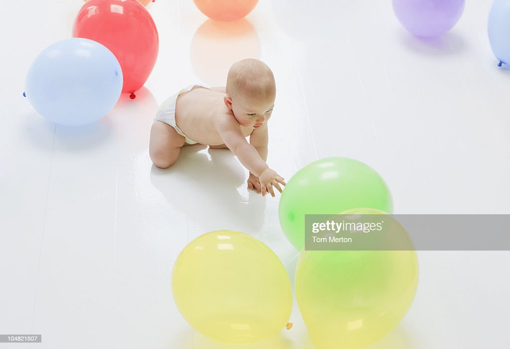 Baby reaching for balloons on floor : Stock Photo