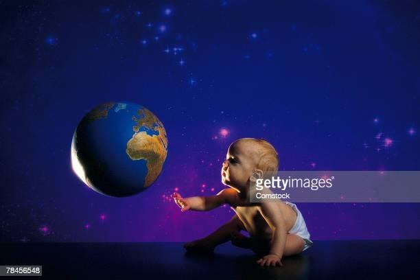 Baby reaching for globe