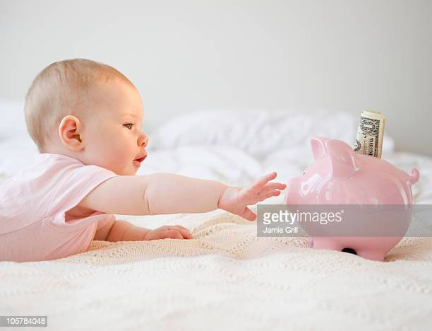 Baby reaching for piggy bank