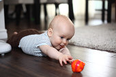 Baby boy lying on his stomach on the floor reaching out to a toy and learning to crawl. See more in my profile.