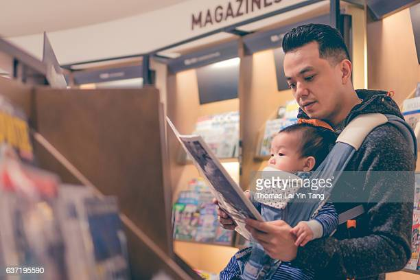 Baby reading book with father at book store