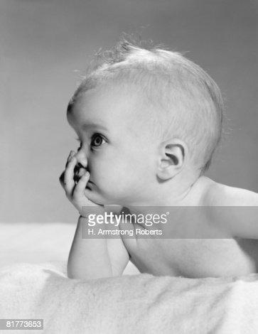 Baby resting chin on hand, portrait. : Stock Photo
