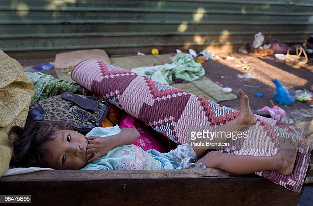 A baby rests in the cart that the family uses to keep all of their belongings in February 7 2010 in Phnom Penh Cambodia The child sleeps on the...