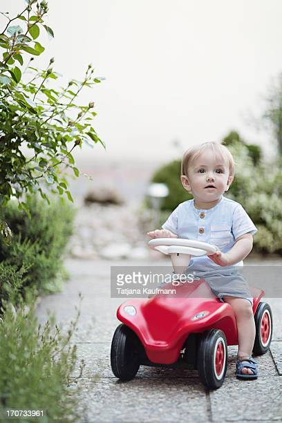 Baby riding a Toy Car in Front Garden