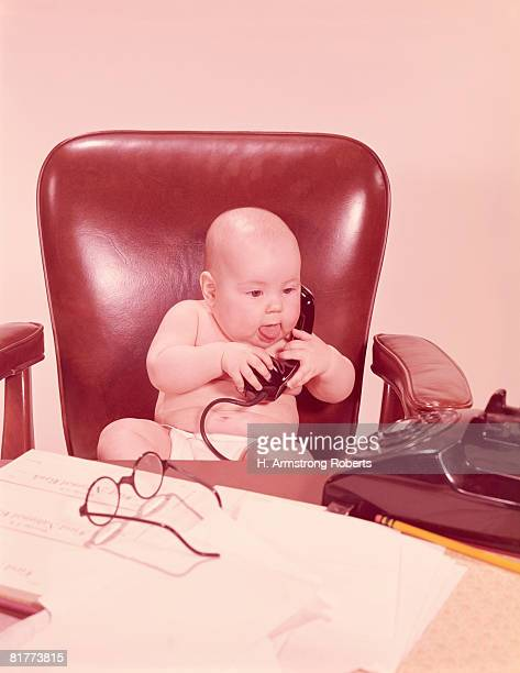 Baby sat at office desk, holding telephone. (Photo by H. Armstrong Roberts/Retrofile/Getty Images)