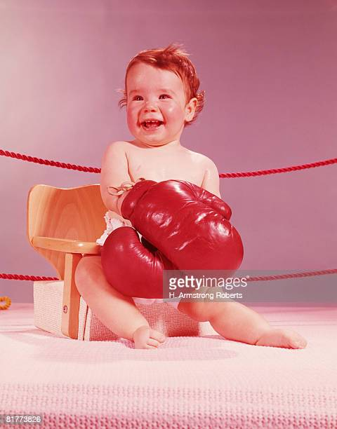 Baby sat on chair in boxing ring, wearing boxing gloves, smiling. (Photo by H. Armstrong Roberts/Retrofile/Getty Images)