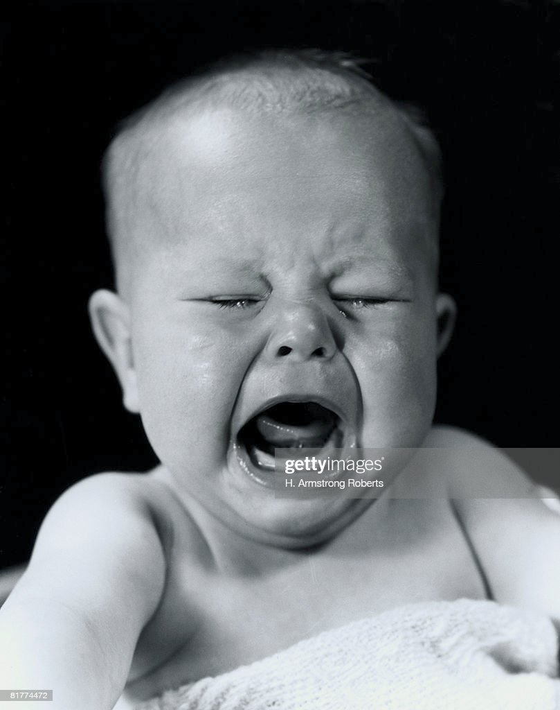 Baby screaming and crying with eyes shut tight. : Stock Photo