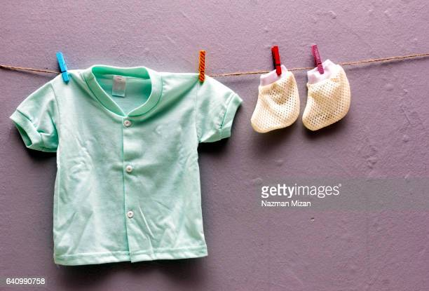 Baby shirt and socks on clotheslines on plain gray background.