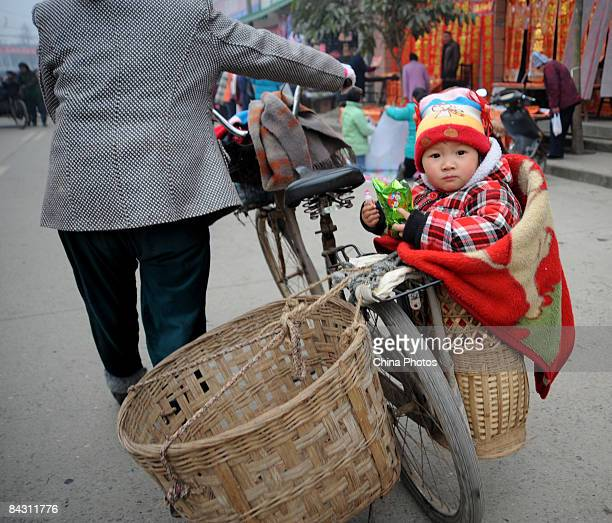 A baby sits in a basket on his way home after shopping for spring festival couplets at the Qingbaijiang District on January 16 2009 in Chengdu of...