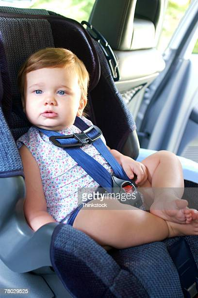A baby sits in a rear facing car seat in the back seat of the car