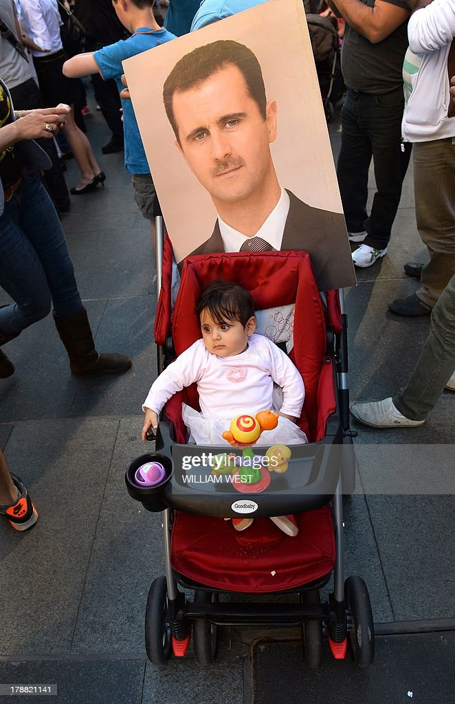 A baby sits in her pram carrying an image of Syrian President Bashar al-Assad during a protest against a possible US military strike against Syria, in Sydney on August 31, 2013. Carrying placards reading 'Hands off Syria' and bearing the face of Syrian President Bashar al-Assad, protesters gathered in Sydney's Martin Place to voice their concerns about a US military assault. AFP PHOTO/William WEST