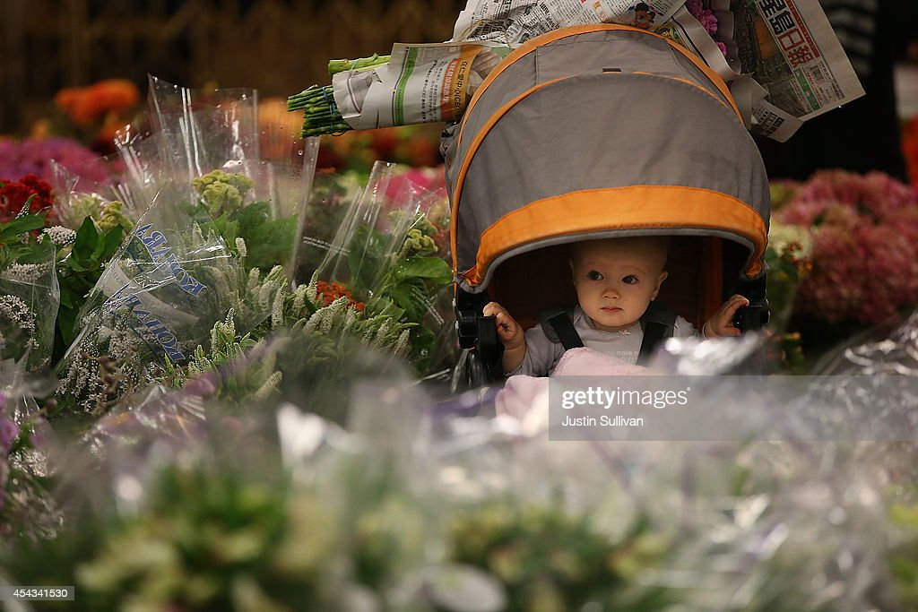 A baby sits in its carriage next to flowers at the San Francisco Flower Mart on August 29, 2014 in San Francisco, California. The future of more than 100 flower businesses at the historic San Francisco Flower Mart hangs in the balance as Los Angeles based realty group Kilroy Realty Corp. is planning on purchasing the Flower Mart property. Kilroy has proposed a plan to build a tech campus on the site.