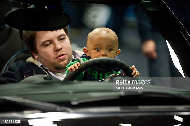 A baby sits on his father's lap at the wheel of a car at the Washington Auto Show at the Walter E Washington Convention Center in Washington on...