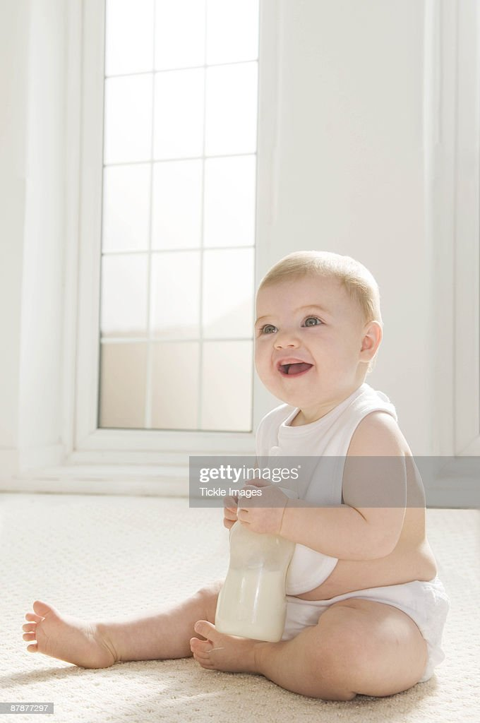 A baby sitting holding a milk bottle. : Stock Photo