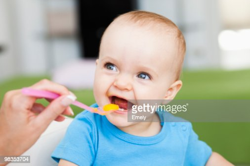 baby sitting in chair being fed