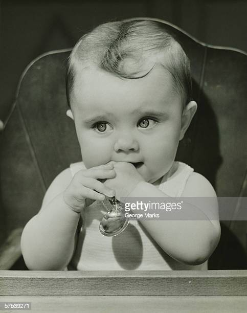 Baby (6-9 months) sitting in high chair, holding spoon, (B&W), portrait