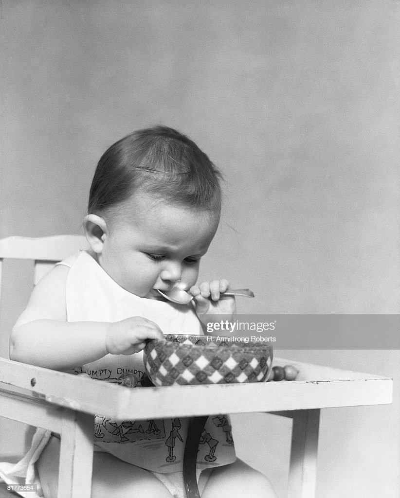 Baby sitting in highchair, eating food from bowl. : Stock Photo