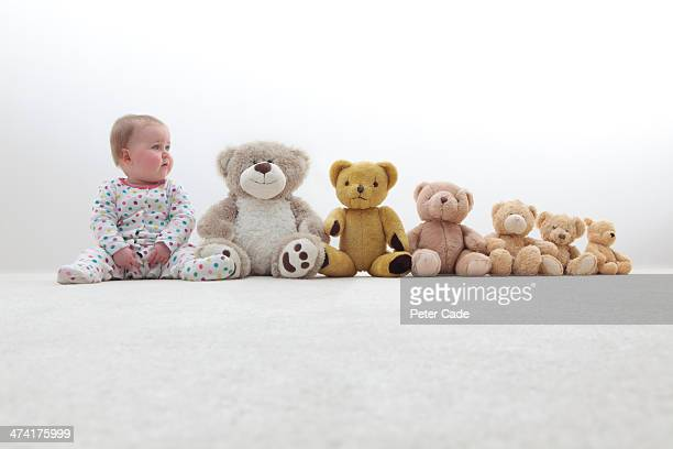 Baby sitting in line with teddy bears