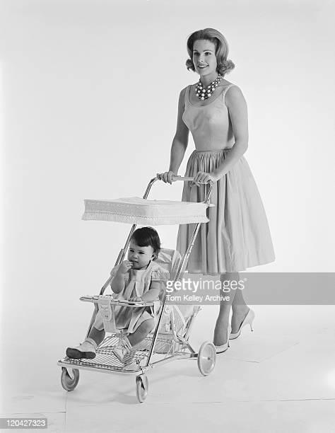 Baby sitting in pram and mother pushing