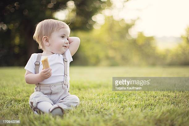 Baby sitting in short Grass with Snack in his Hand