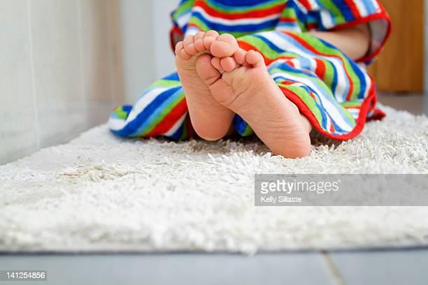 Baby sitting on bath mat