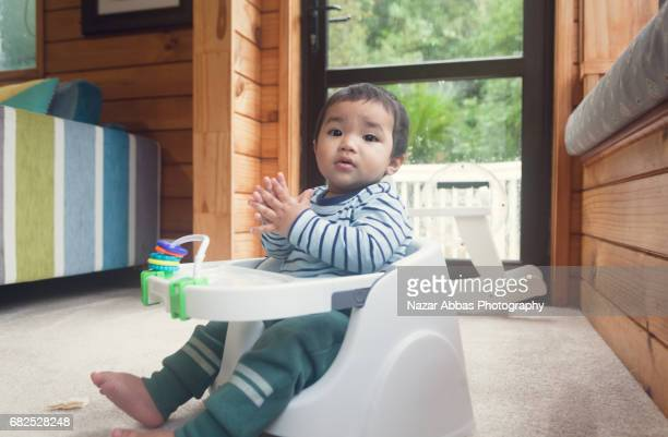 Baby Sitting On Booster Seat And Clapping.