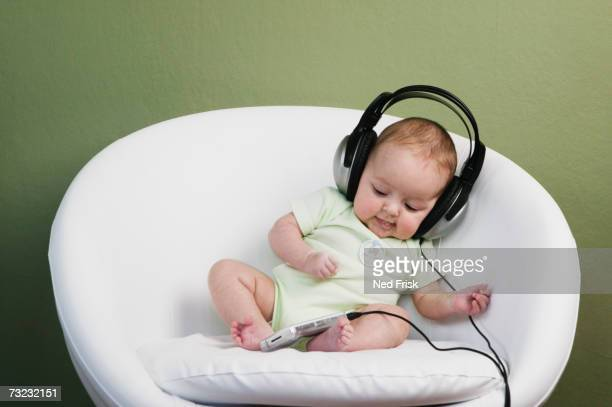 Baby sitting on chair wearing adult headphones