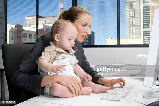 Baby sitting on desk of a businesswoman