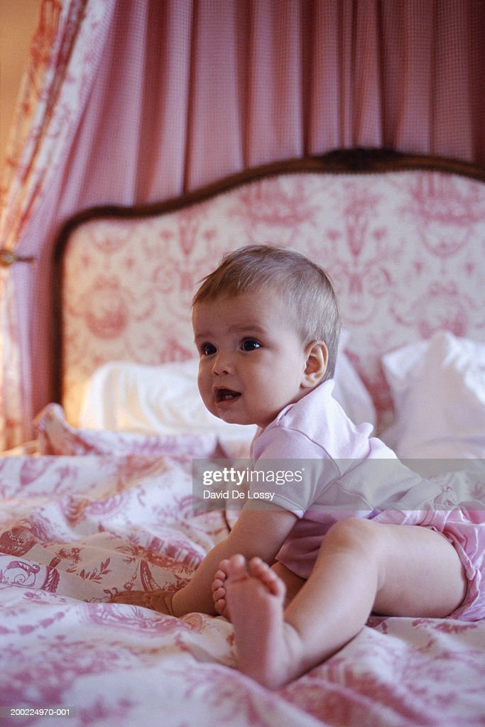 Baby (6-9 months) sitting up on bed : Stock Photo