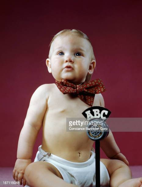 A baby sitting wearing a bow tie with an ABC microphone 9th May 1947