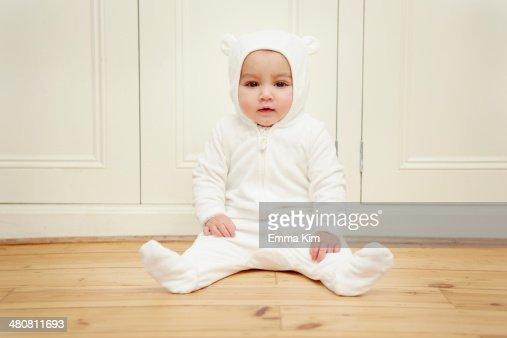 Baby sitting wearing bear babygro