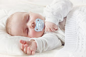 little boy sleeping on soft white blanket. 7 month old baby asleep