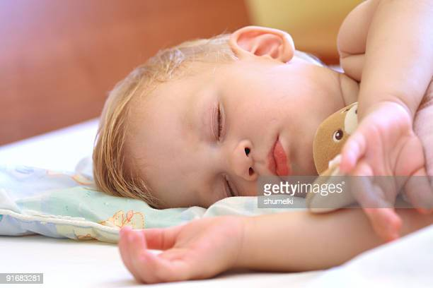Baby sleeping in bed with Teddy Bear