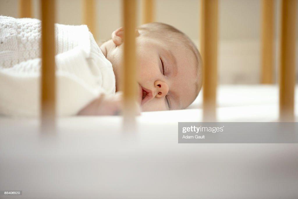 Baby sleeping in crib : Stock Photo