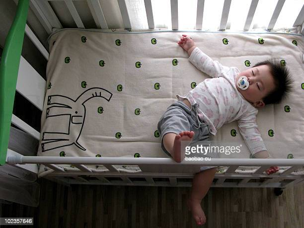 Baby sleeping in the crib with pacifiers