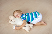 Baby sleeping on wooden floor with stuffed toy sheep and milk bottle. Funny tired little boy falling asleep crawling on hardwood floor at home. Sleepy infant drinking formula on soft cushion.