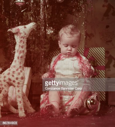 Baby sleeping under Christmas tree covered in tinsel