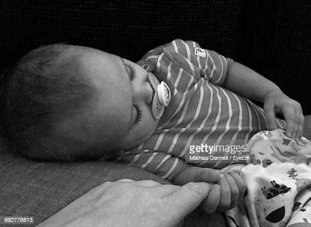 Baby Sleeping While Holding Parent Finger At Home