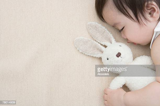 A baby sleeping with a stuffed animal