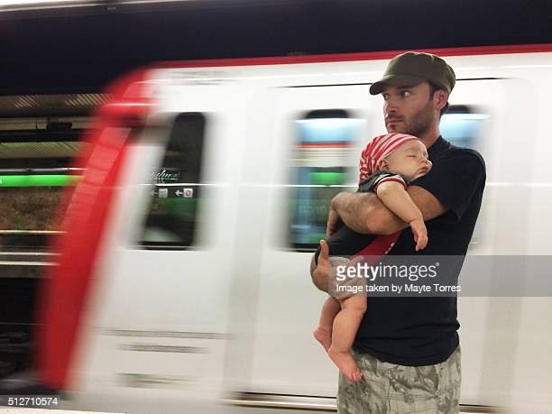 Baby sleeping with dad at the tube station