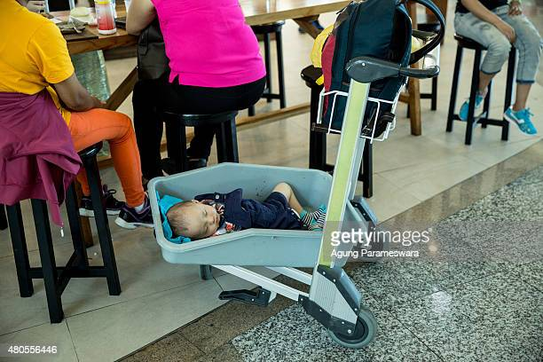 A baby sleeps at Ngurah Rai International airport departure on July 13 2015 in Denpasar Bali Indonesia Bali's international airport reopened after...