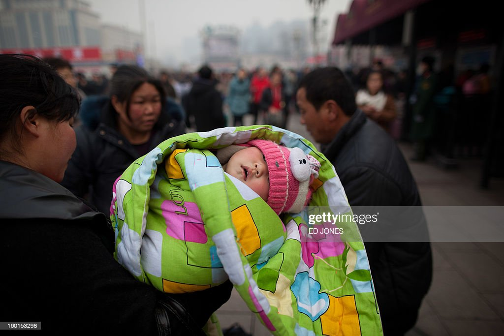 A baby sleeps in the arms of woman at Beijing Railway Station in Beijing on January 27, 2013. The world's largest annual migration began in China with tens of thousands in the capital boarding trains to journey home for next month's Lunar New Year celebrations. AFP PHOTO / Ed Jones