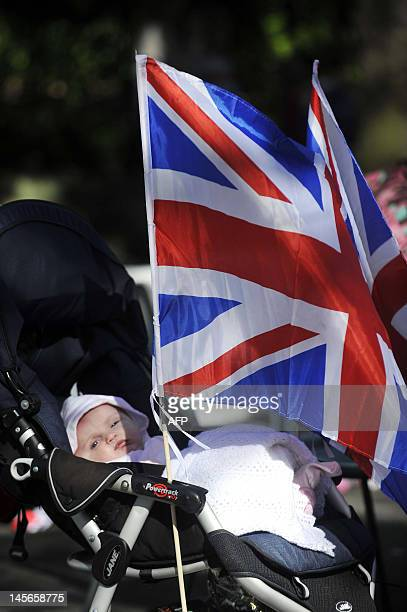 A baby sleeps next to a Union Jack flag during a street party to celebrate the Queen's Diamond Jubilee in Edinburgh on June 3 2012 Britain is...