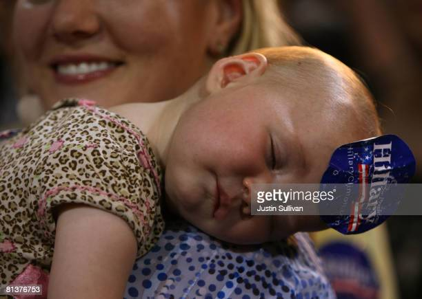 A baby sleeps while wearing a 'Hillary' campaign sticker during a rally for Democratic presidential hopeful US Sen Hillary Clinton at the WH Lyon...