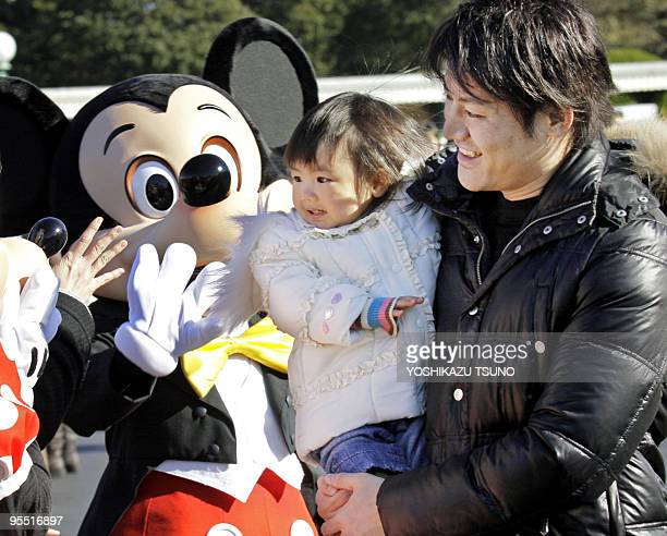 A baby smiling in her father's arms is greeted by Disney character Mickey Mouse for New Year Day greetings at Tokyo Disneyland in Urayasu Chiba...