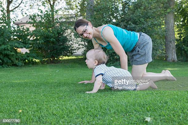 Baby son with his mother crawling in lawn, Munich, Bavaria, Germany